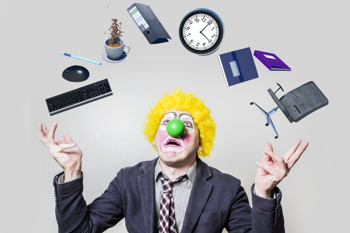 clown raised his hands juggling objects of office life as a symbol of the business agenda